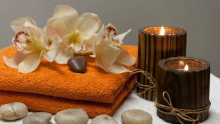 Photo of towels, stones, orchids and candles.