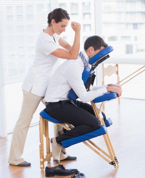 A therapist giving a man a chair massage.
